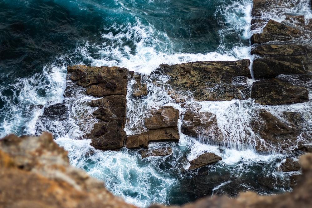 ocean water splashing on rocks during daytime