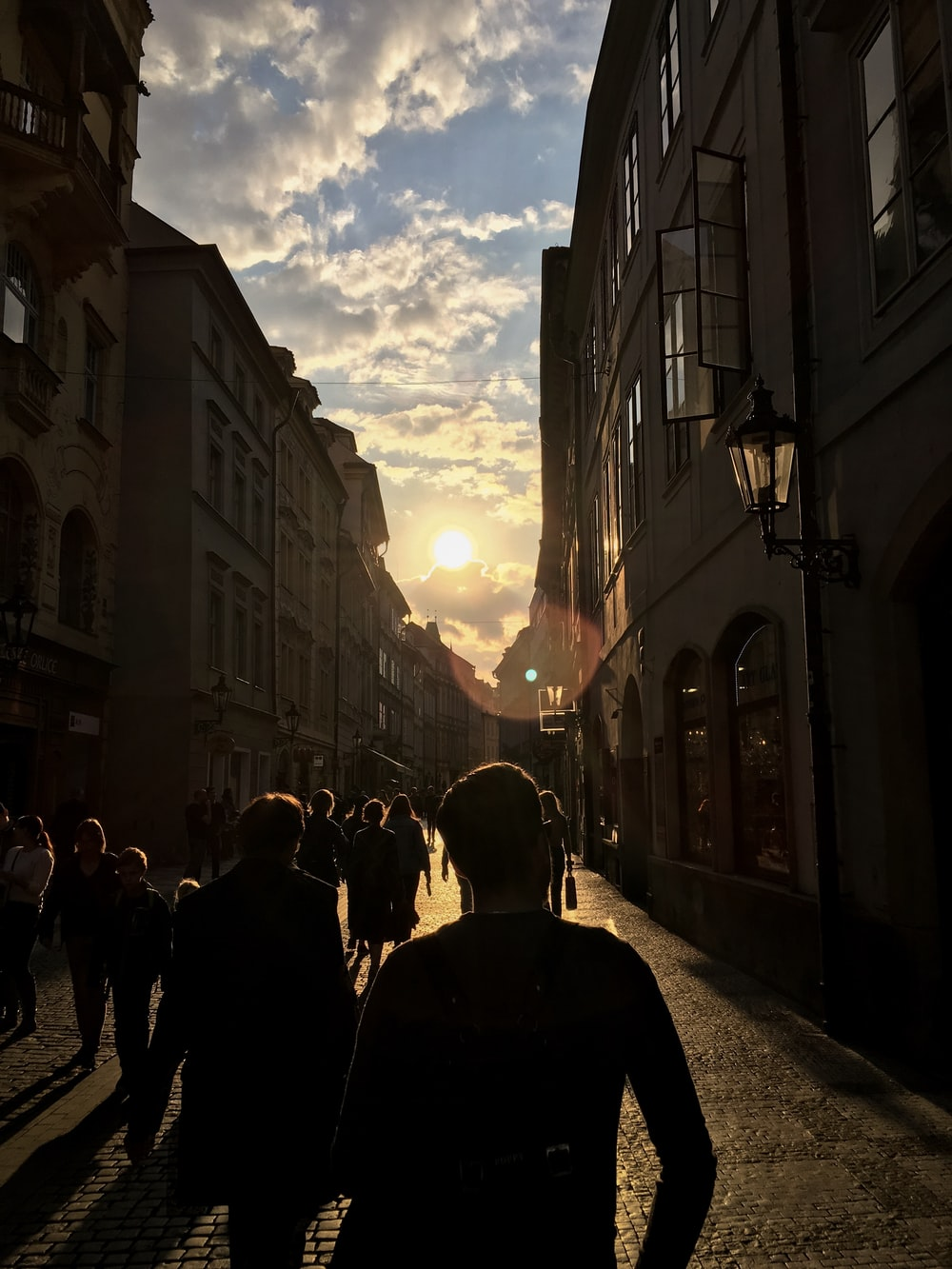 people walking near buildings during golden hour