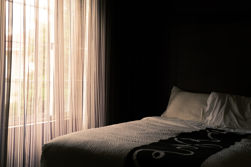 bed near window with curtain