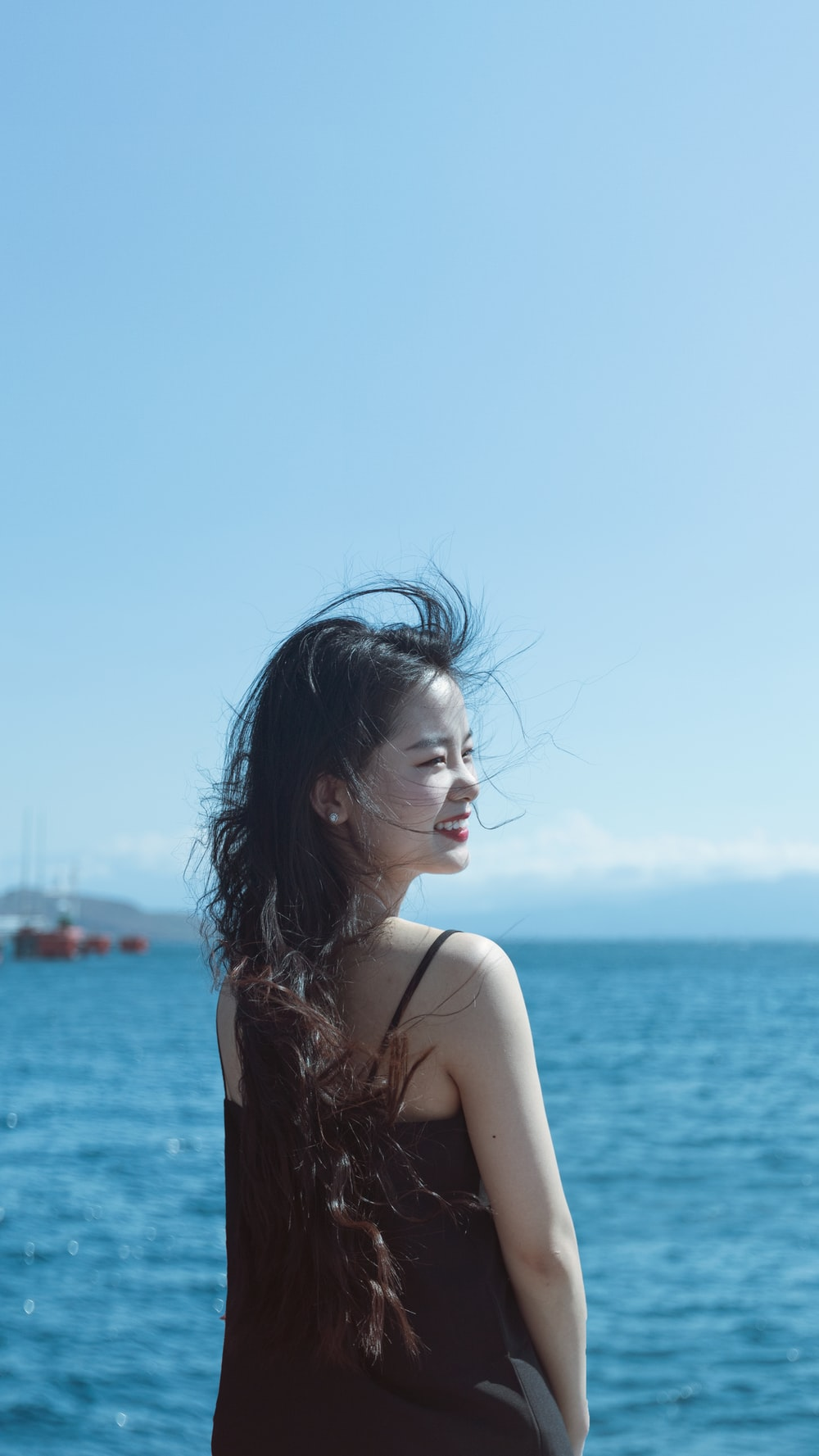 smiling woman standing near body of water during daytime