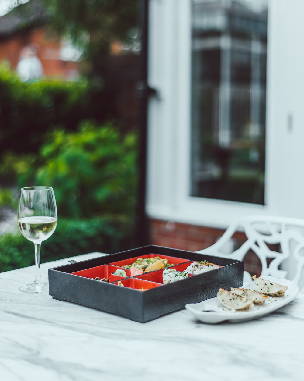 black and red bento box on white table beside of goblet glass