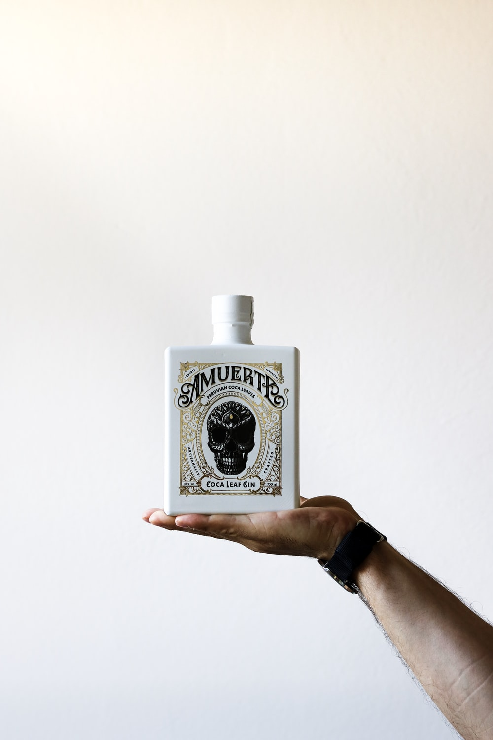 person holding white and black ceramic decanter