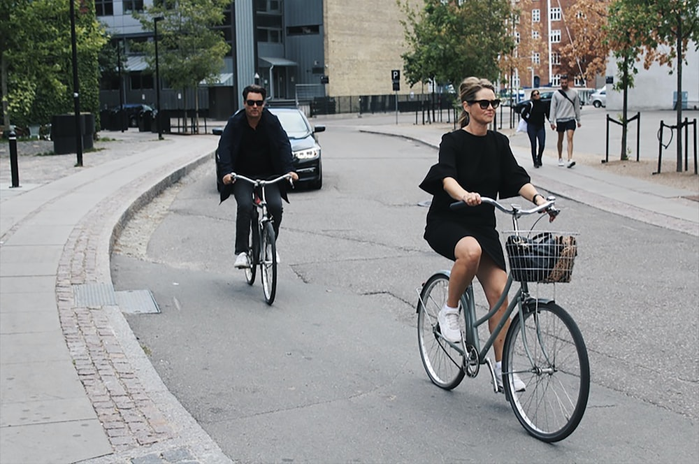 people walking and riding bikes at the street near buildings