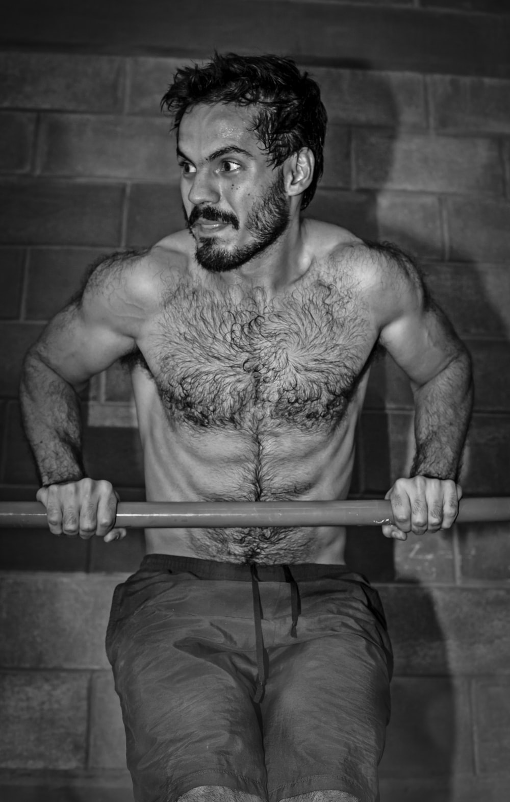grayscale photography of man holding bar