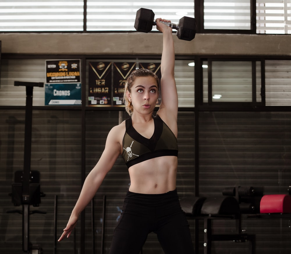 woman exercising with dumbbell inside gym