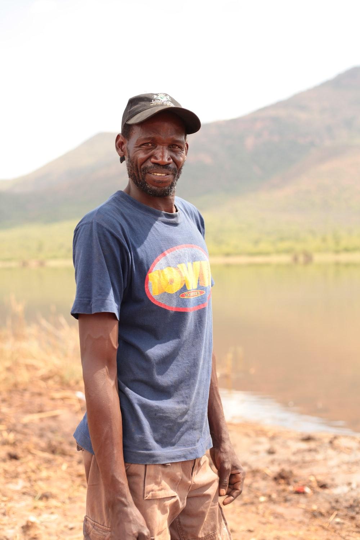 man in blue beside a lake
