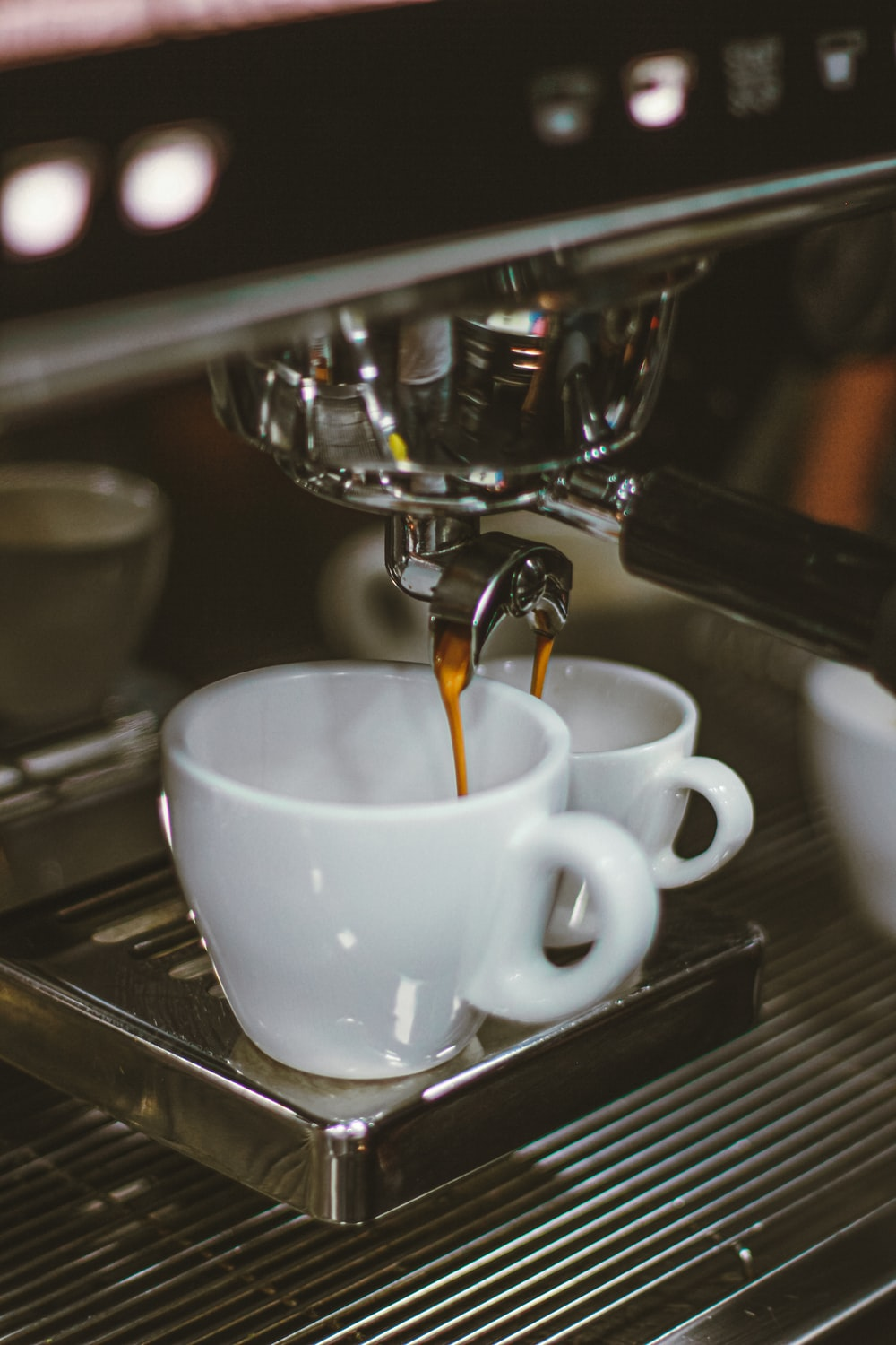 selective focus photography of machine pouring coffee on two mugs
