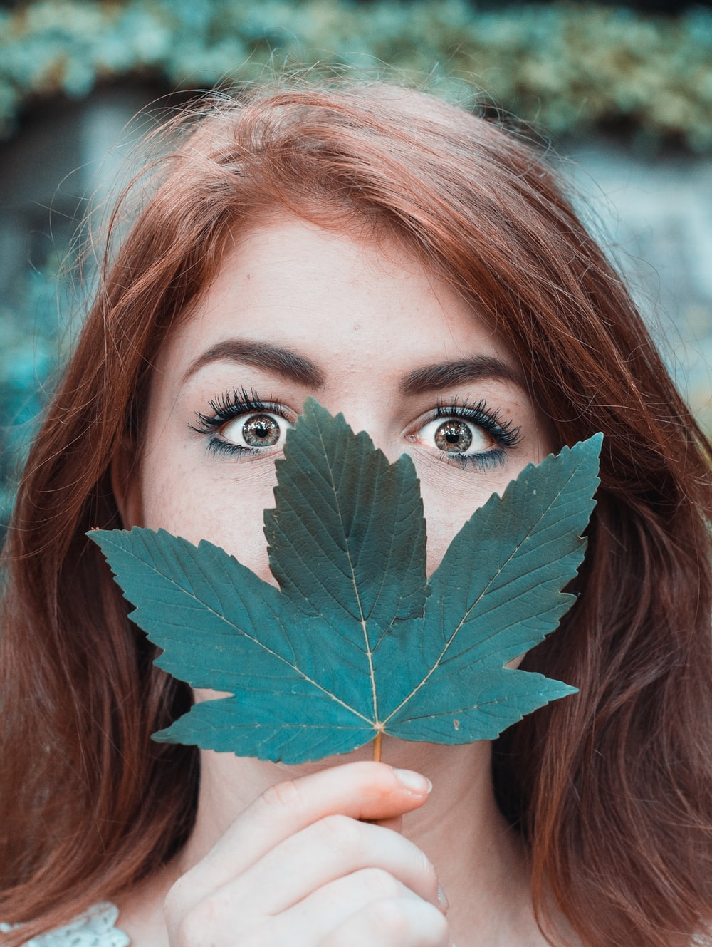 woman covering face with maple leaf