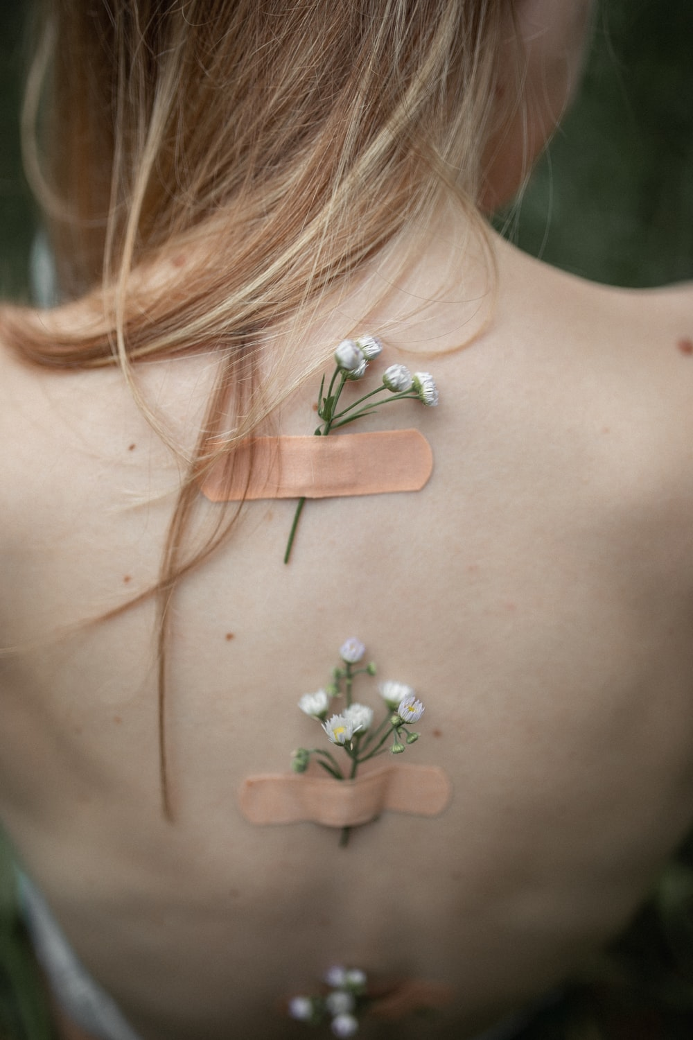 white petaled flowers stuck on a woman's back