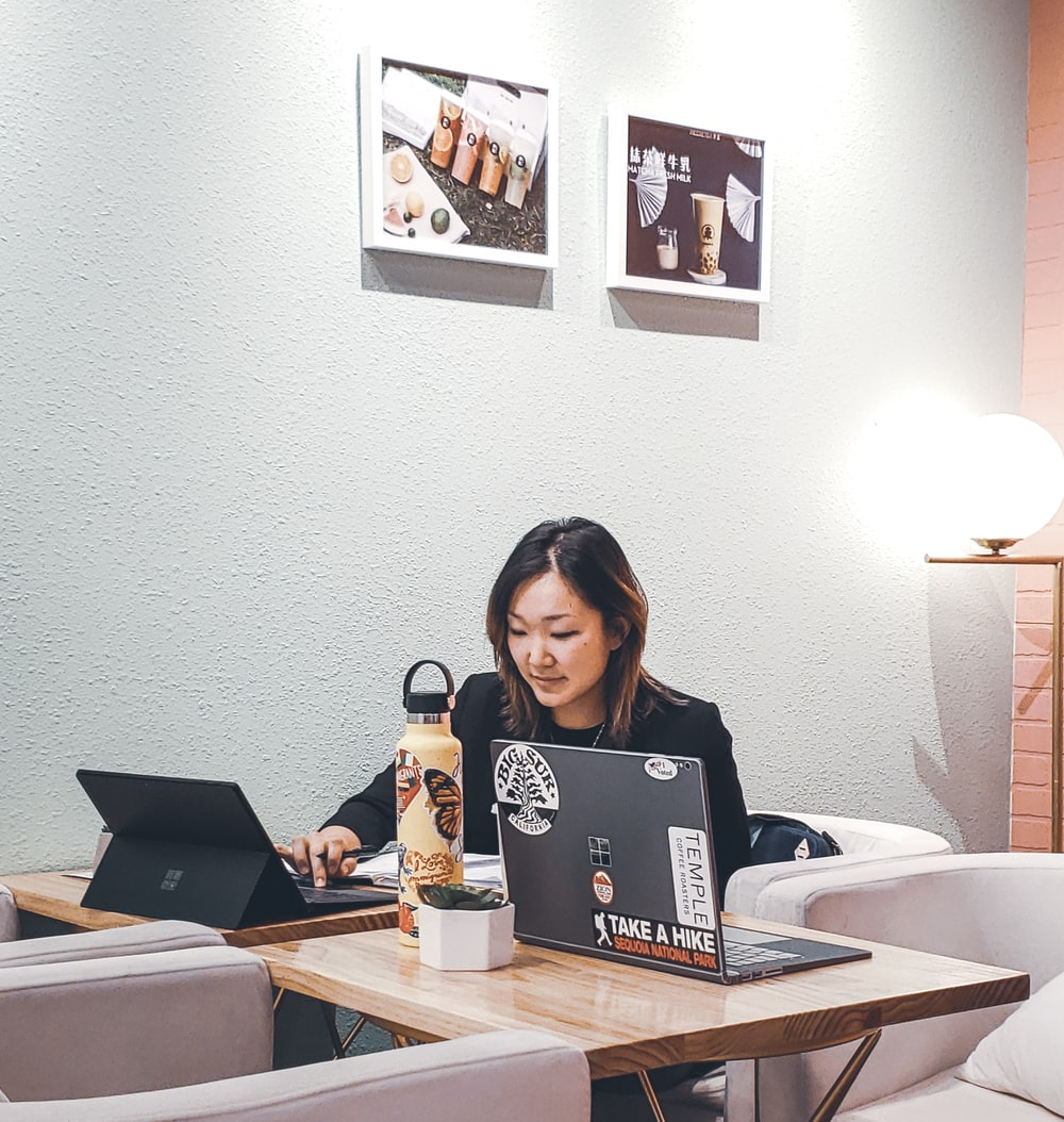 woman sitting behind table with black laptop computer