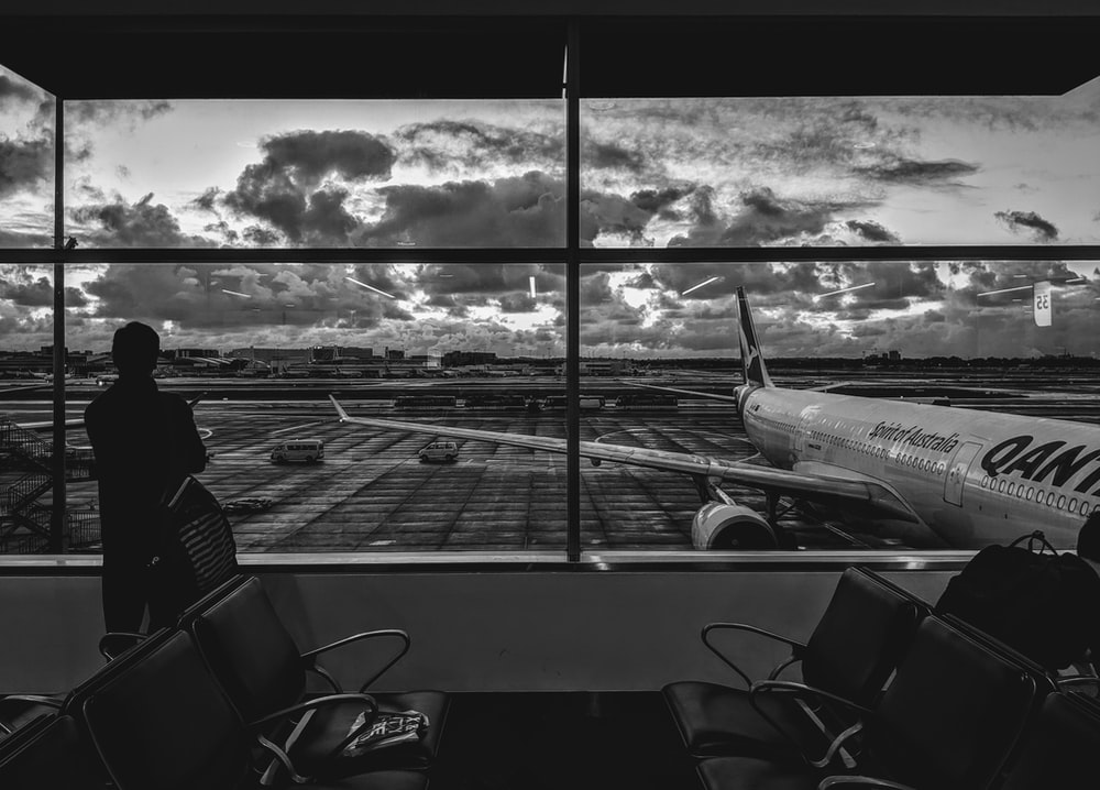 grayscale photography of man standing in front of plane