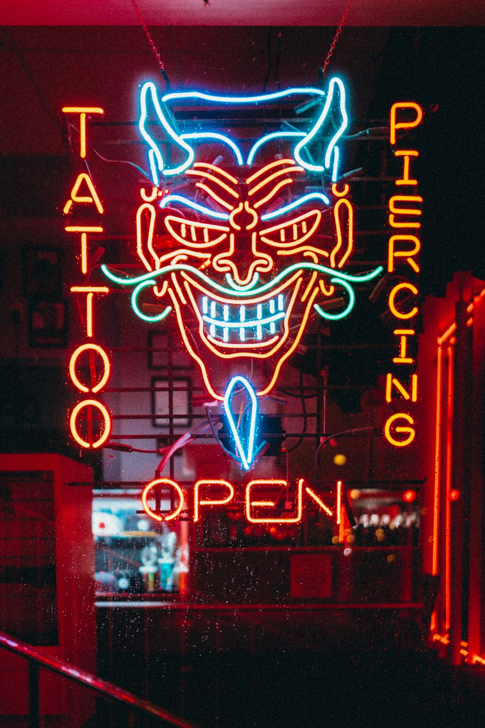 red and blue tattoo piercing open LED sign