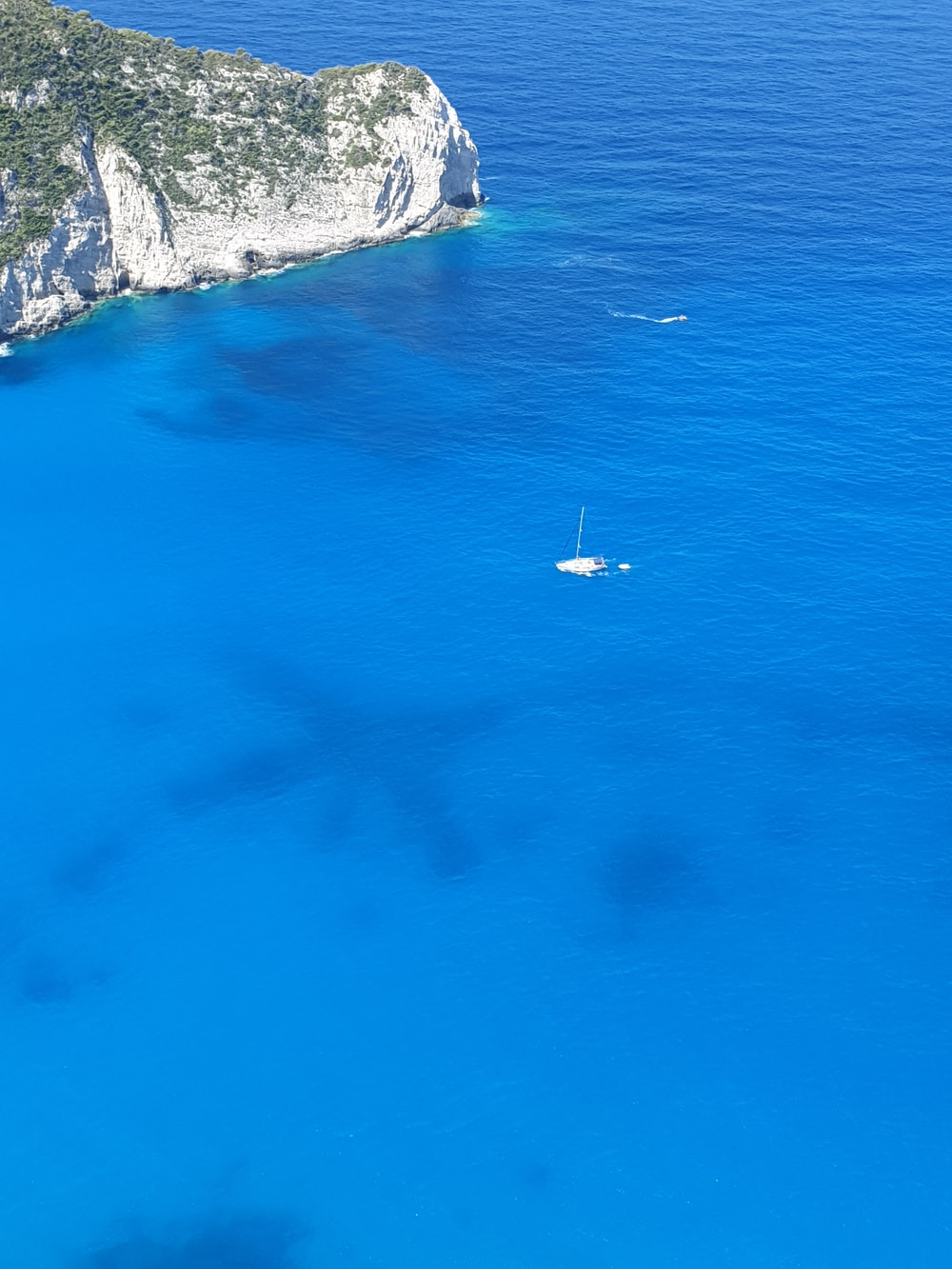 white sailboat in blue sea passing white rock cliff