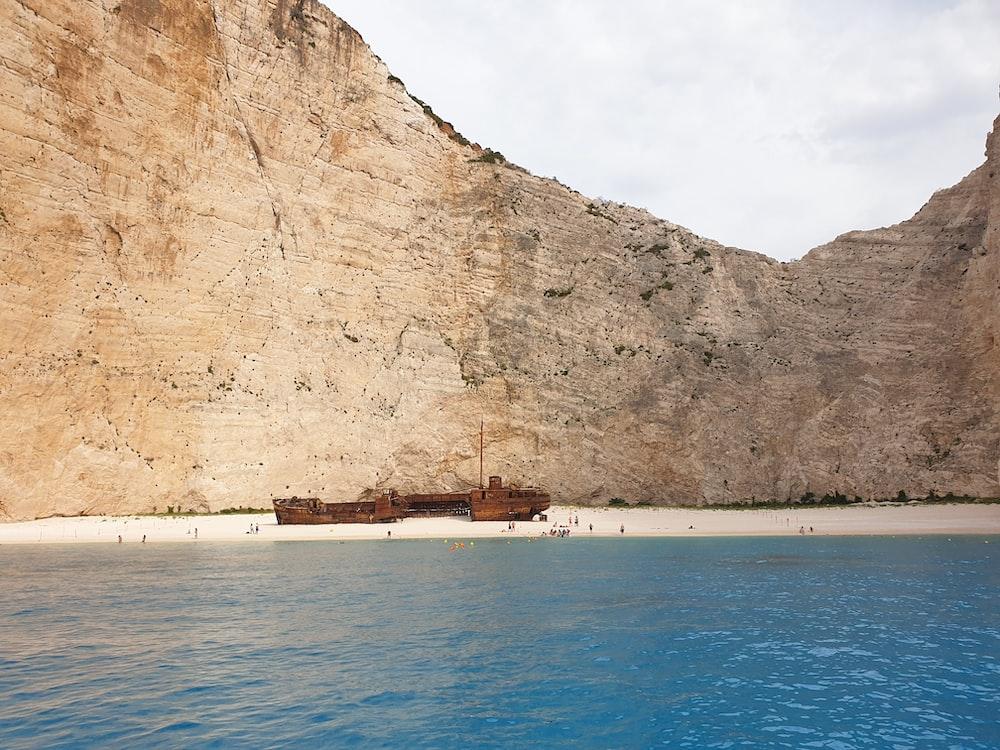 brown ship on shore near brown mountain