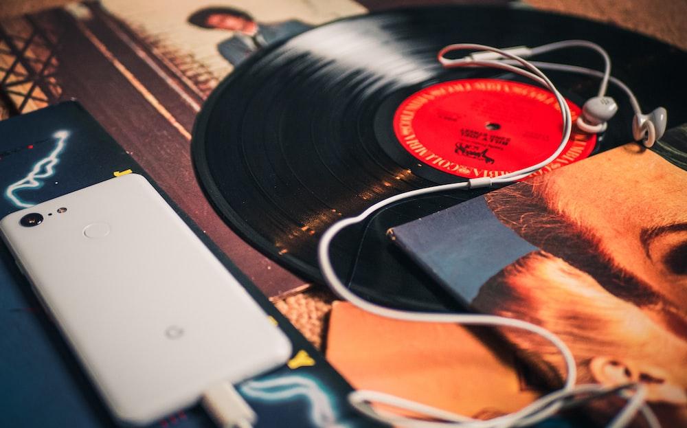 white Google Pixel smartphone beside black vinyl record