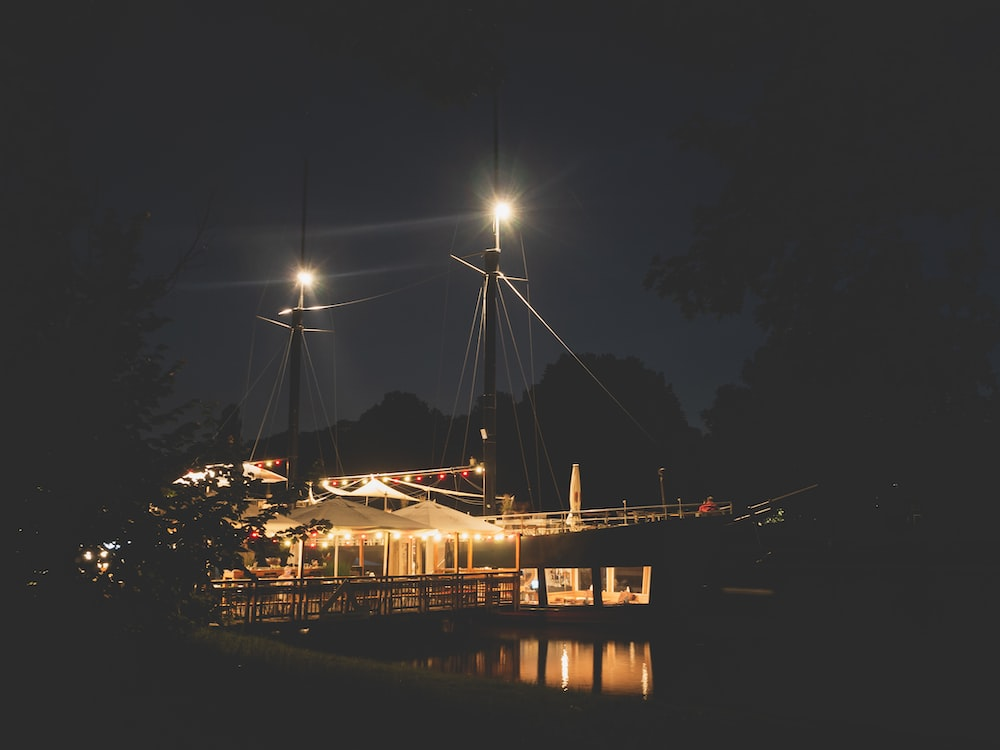 lighted boat masts in dock at night