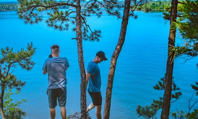 two men standing under trees in bank of lake arkansas teams background