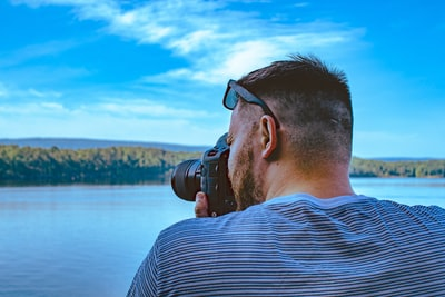 man taking photo of calm sea under blue and white skies arkansas teams background