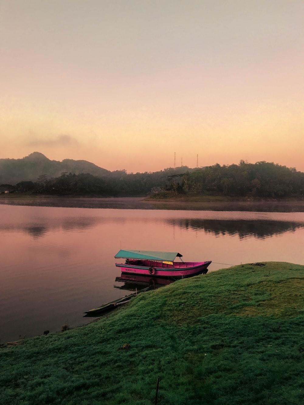 pink boat on body of water beside island