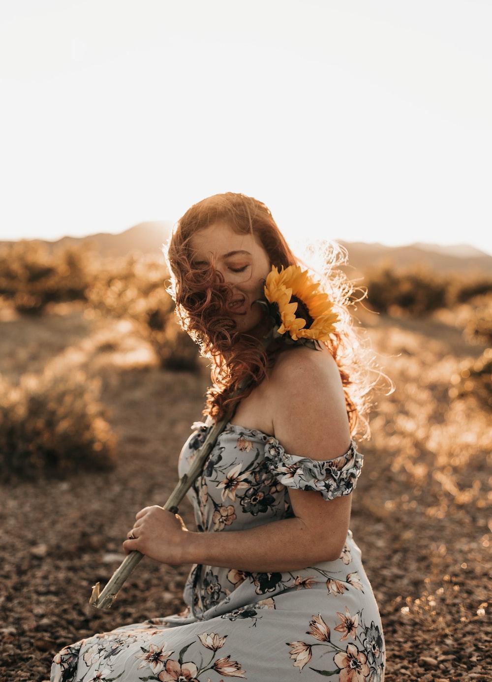 woman holding yellow sunflower sitting on ground