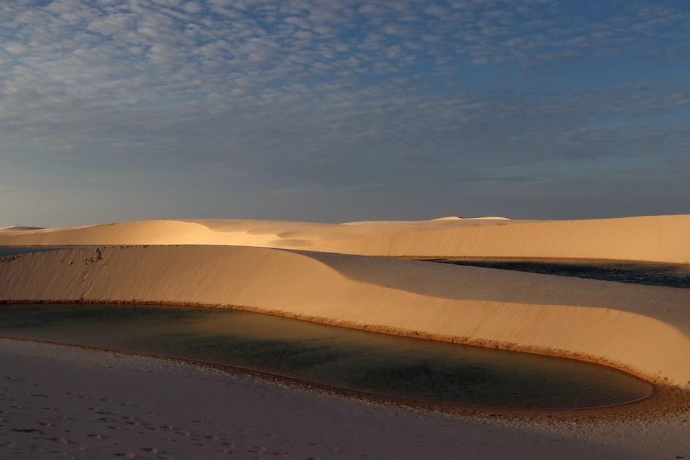 body of water on desert under blue sky