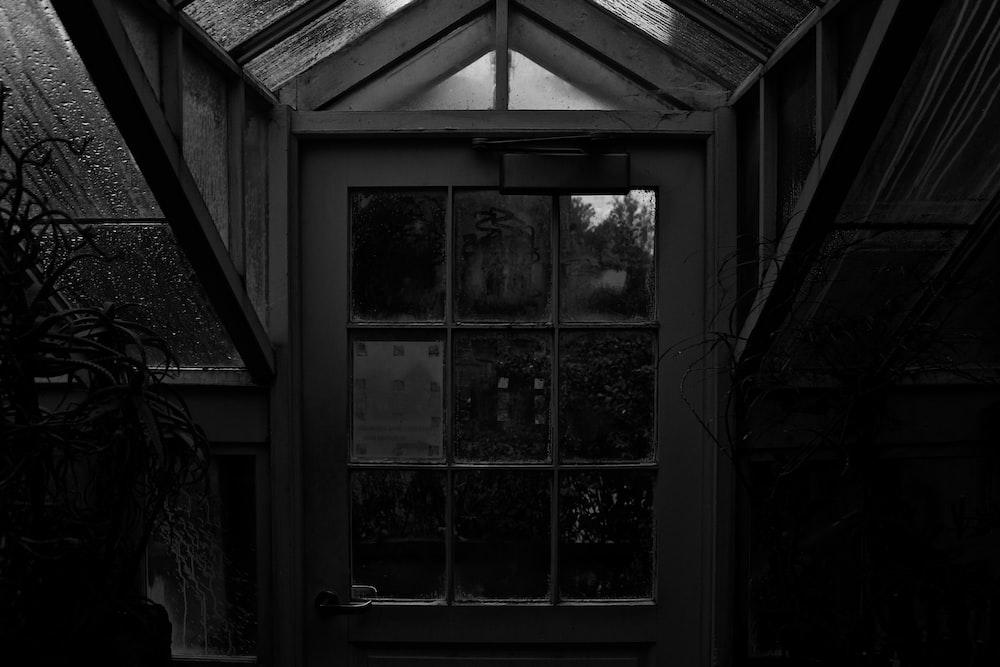 grayscale photo of closed half-lite door
