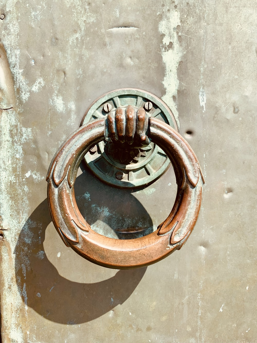 brown and green door knocker close-up photography