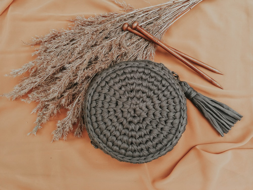 round gray woven purse beside grass and nails
