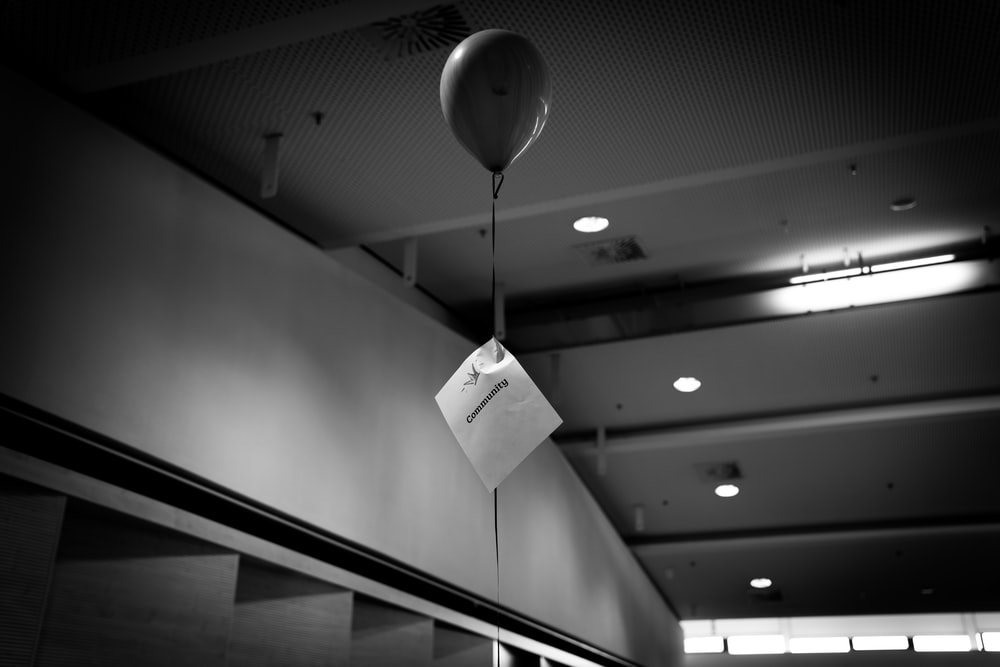 grayscale photography of floating balloon touching the ceiling