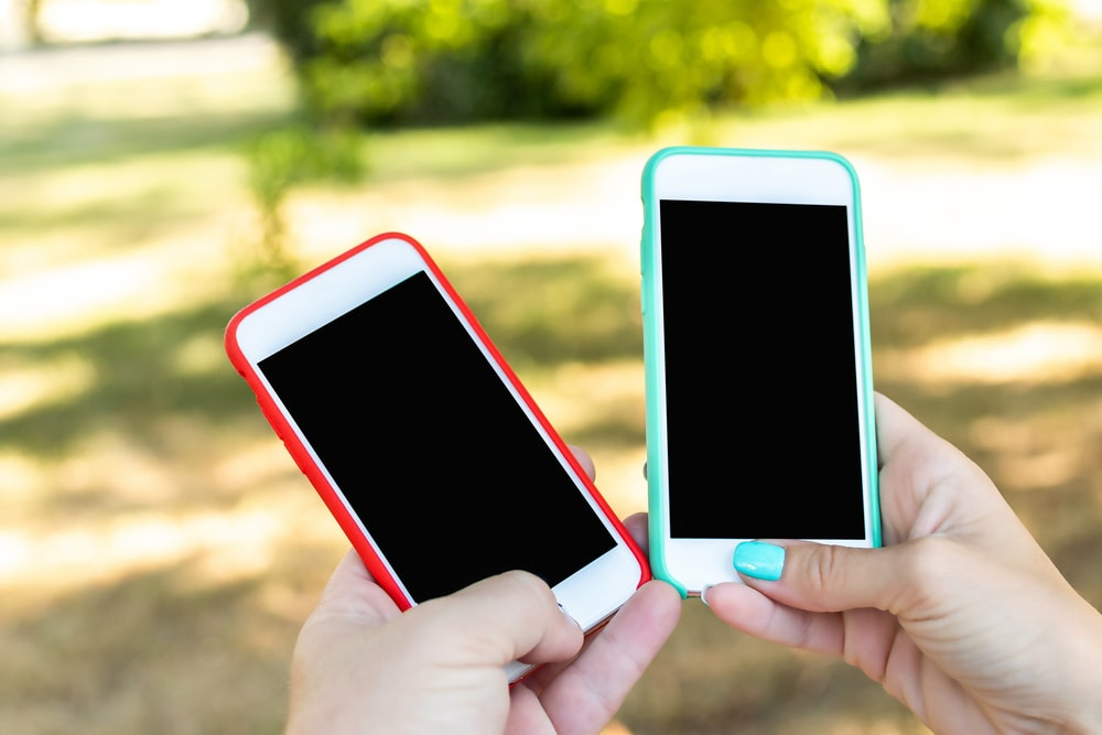 two white smartphone with red and green cases