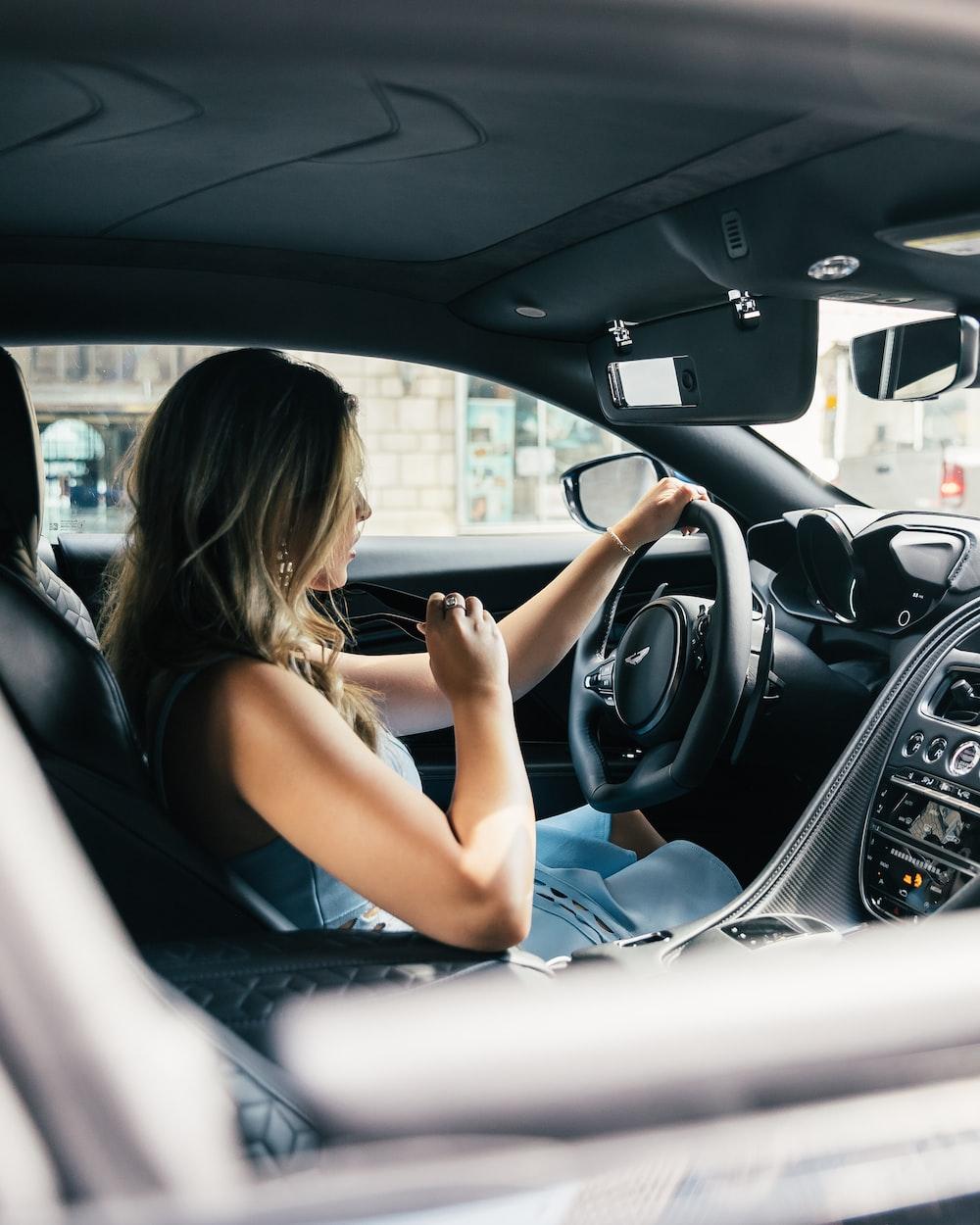 woman wearing white tank top driving vehicle during daytime