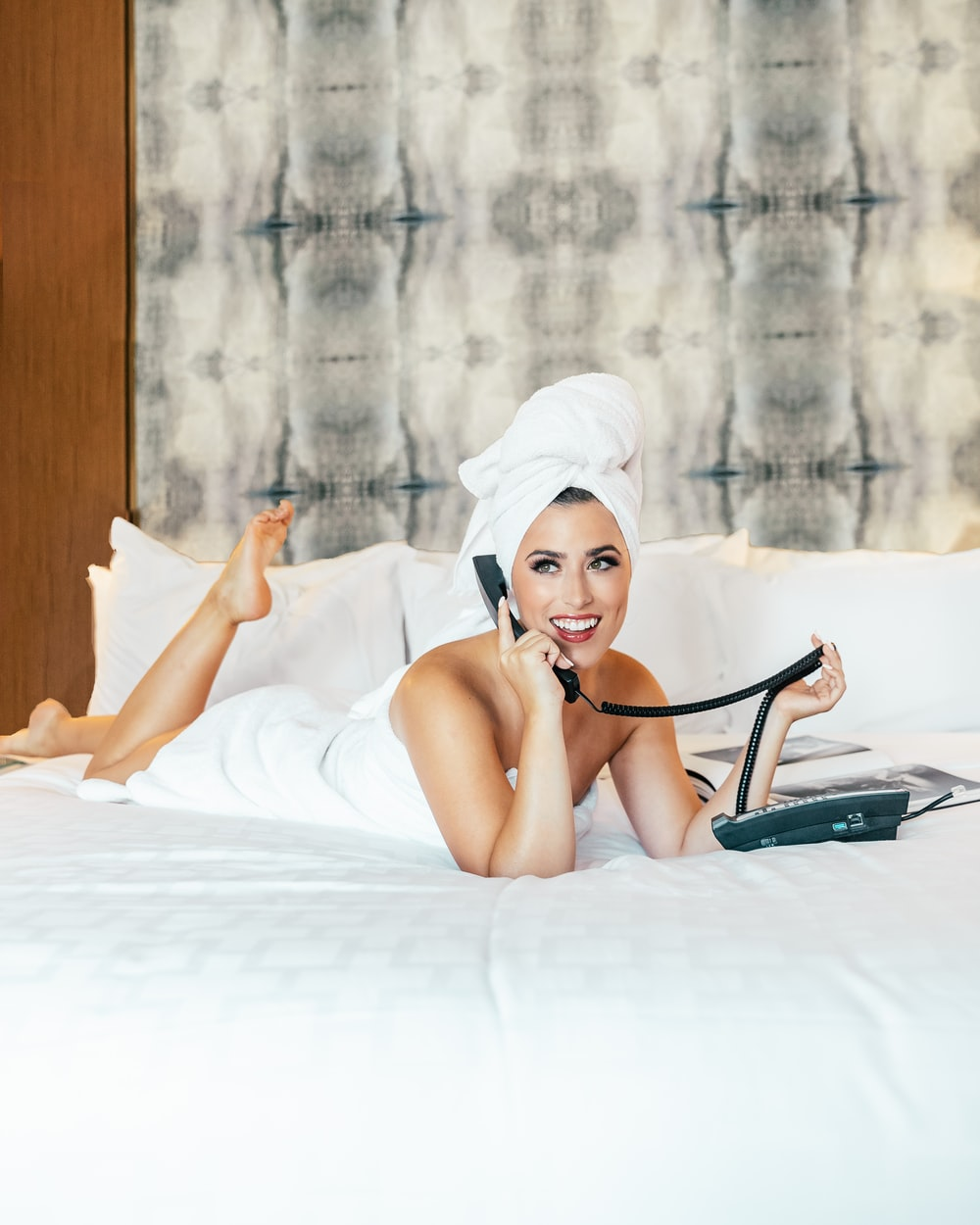 woman wrapped in towel lying on bed talking to desk phone
