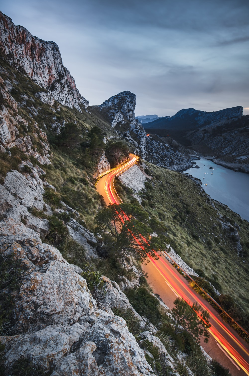 road beside a cliff near body of water during daytime