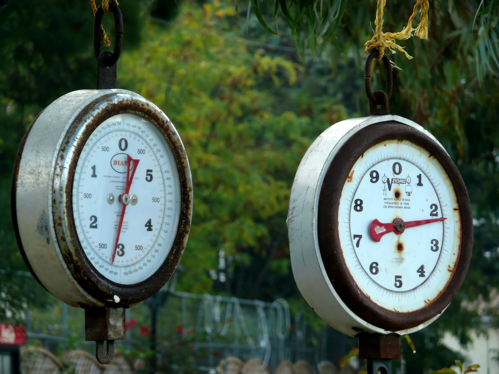 two white round analog weighing scales at 3 and 3