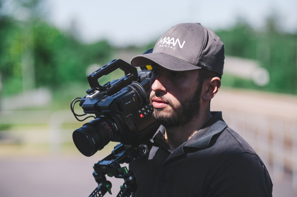 man with video camera on selective focus photography