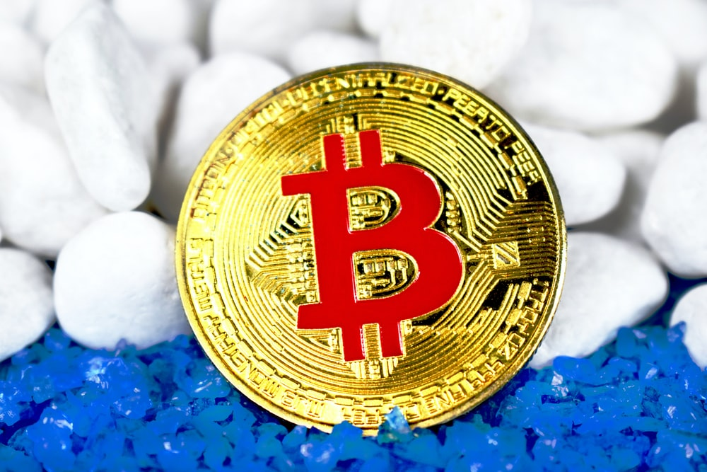 round gold-colored and red Bitcoin coin