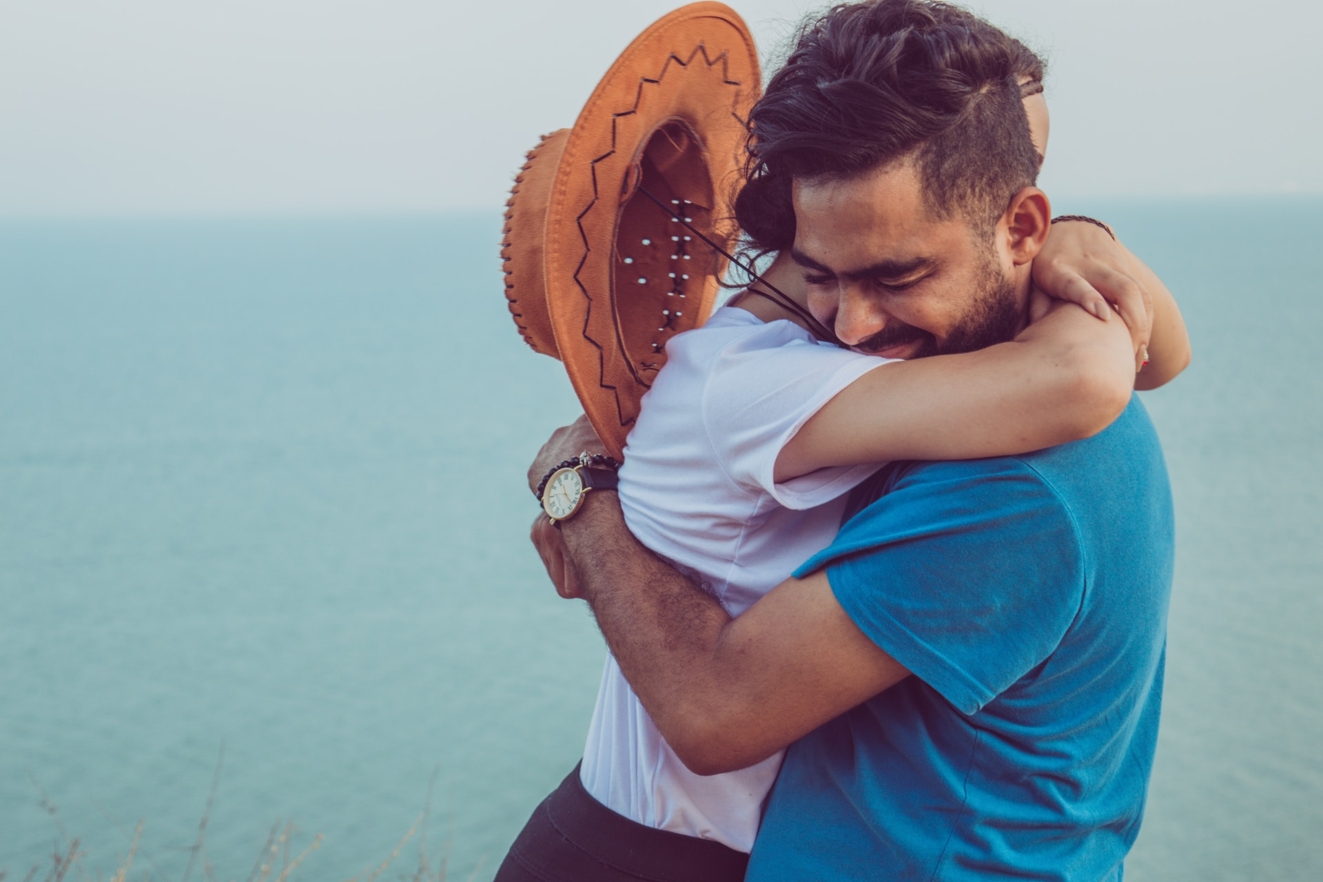 couple hugging on high ground overlooking the sea