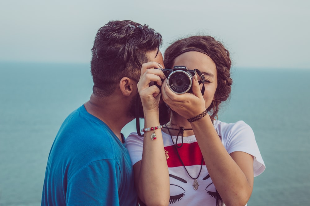 man kissing woman's cheek while taking photo