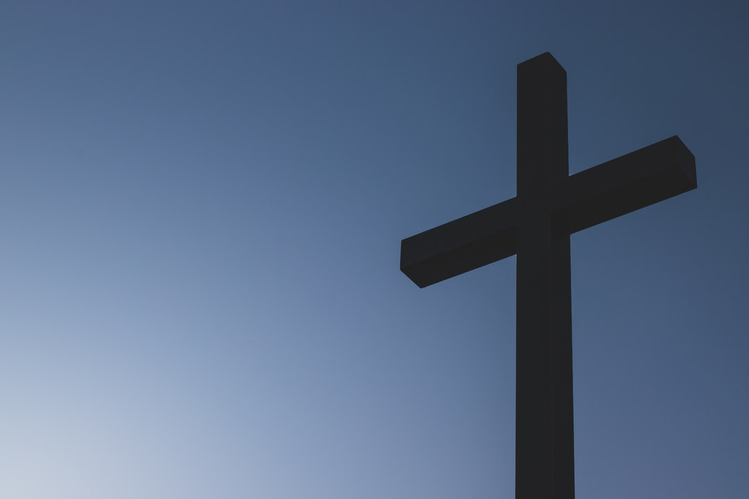 silhouette of cross against the dark sky