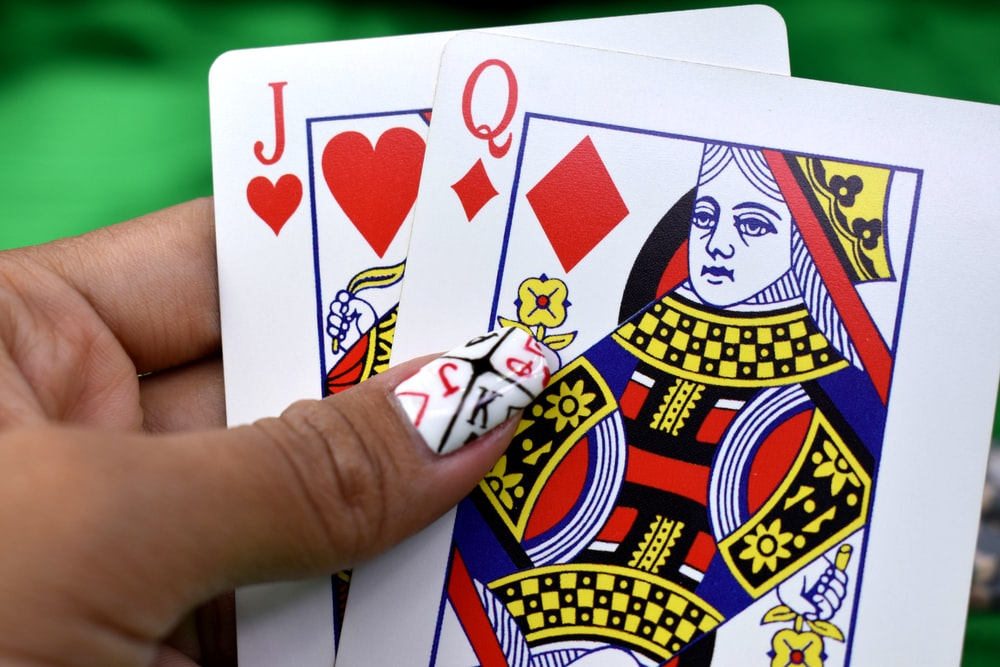 person holding queen of diamonds and jack of hearts playing cards