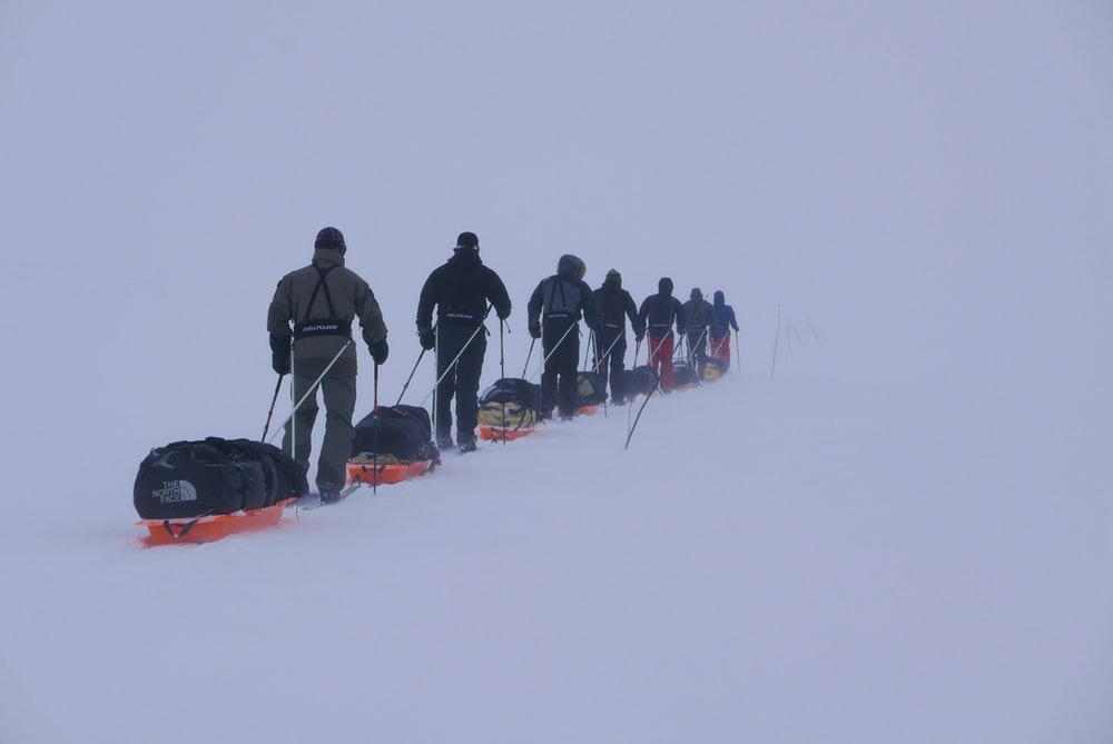 seven men with sleds trekking in line on snow field