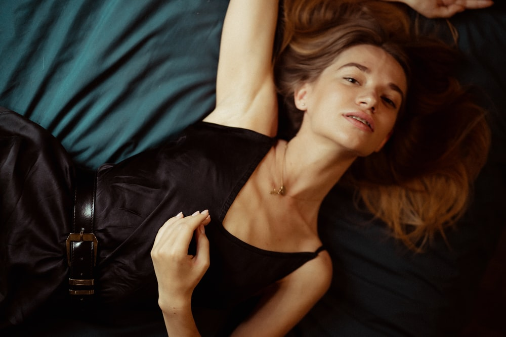 woman lying on bed while wearing black sleeveless dress