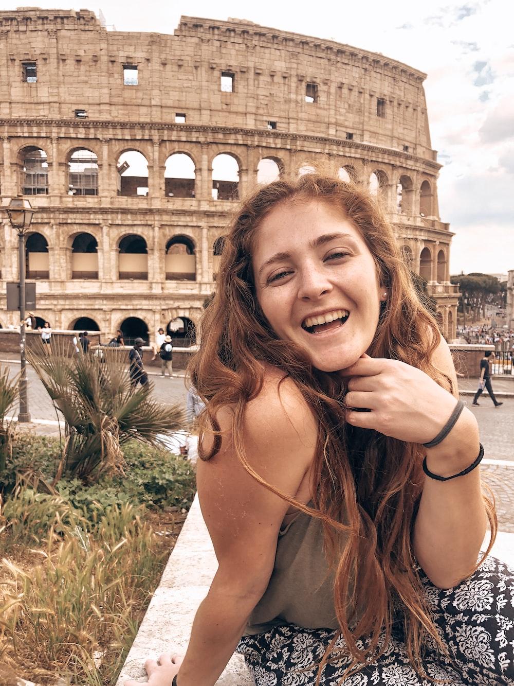 woman smiling near coliseum