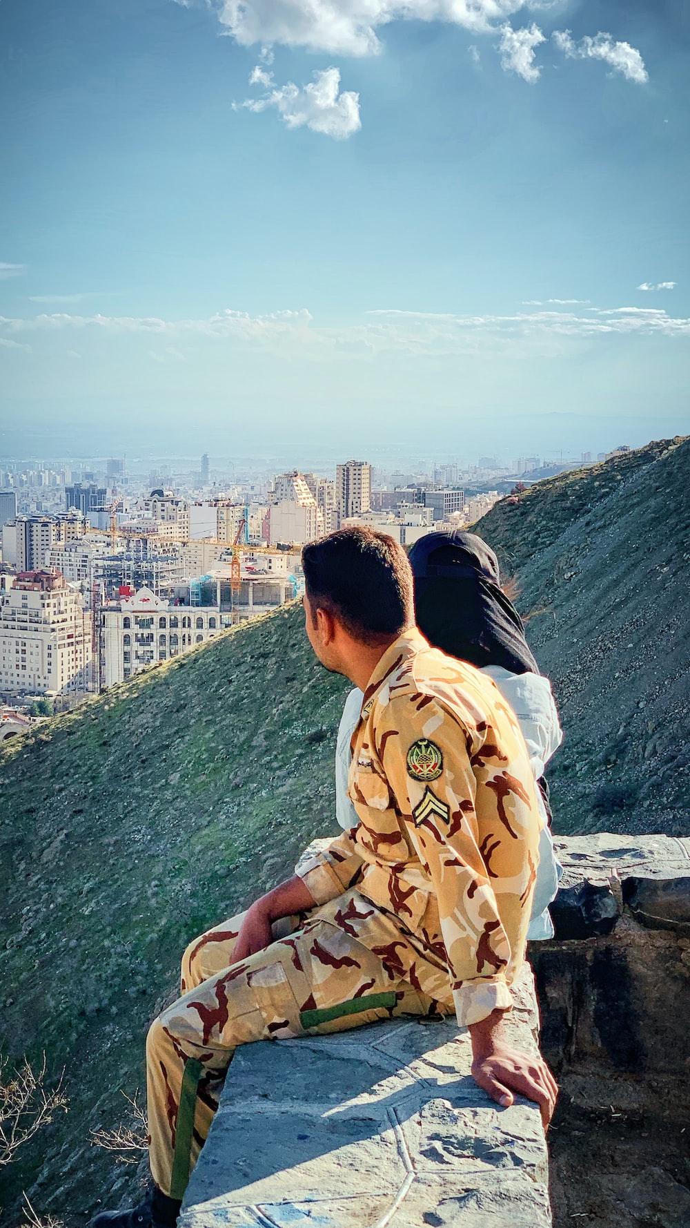 man and woman sitting near hill