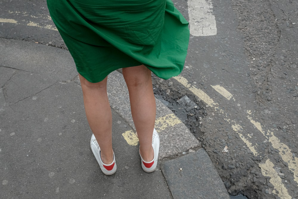 person wearing green dress and pair of white shoes
