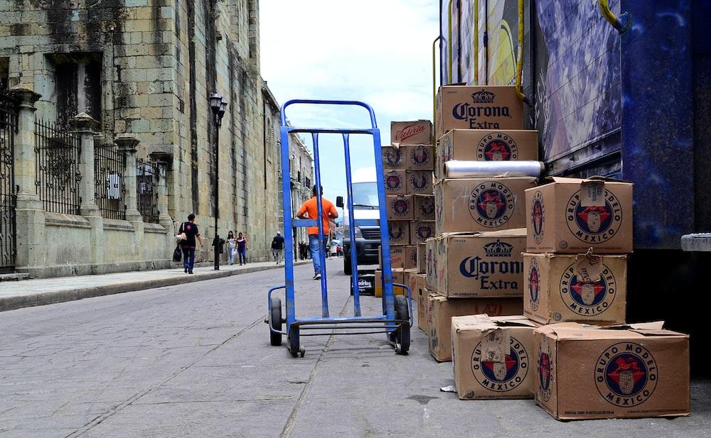 blue hand truck beside cardboard boxes