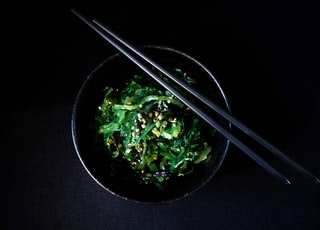vegetable salad in bowl with chopsticks on top of bowl