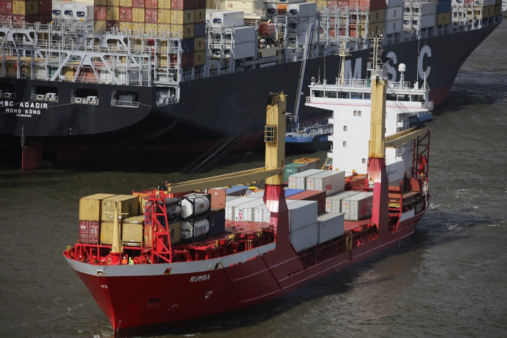 red and white cargo ship beside dock