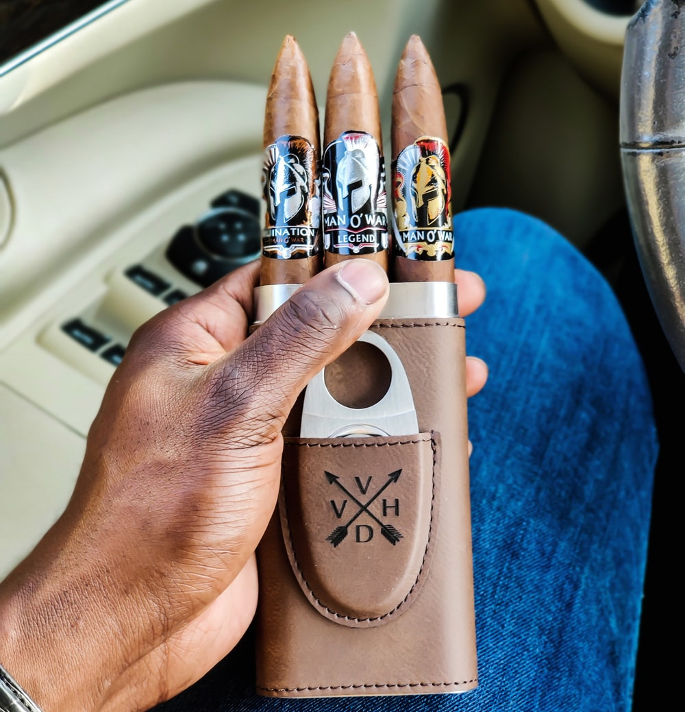 person holding brown leather cigar case