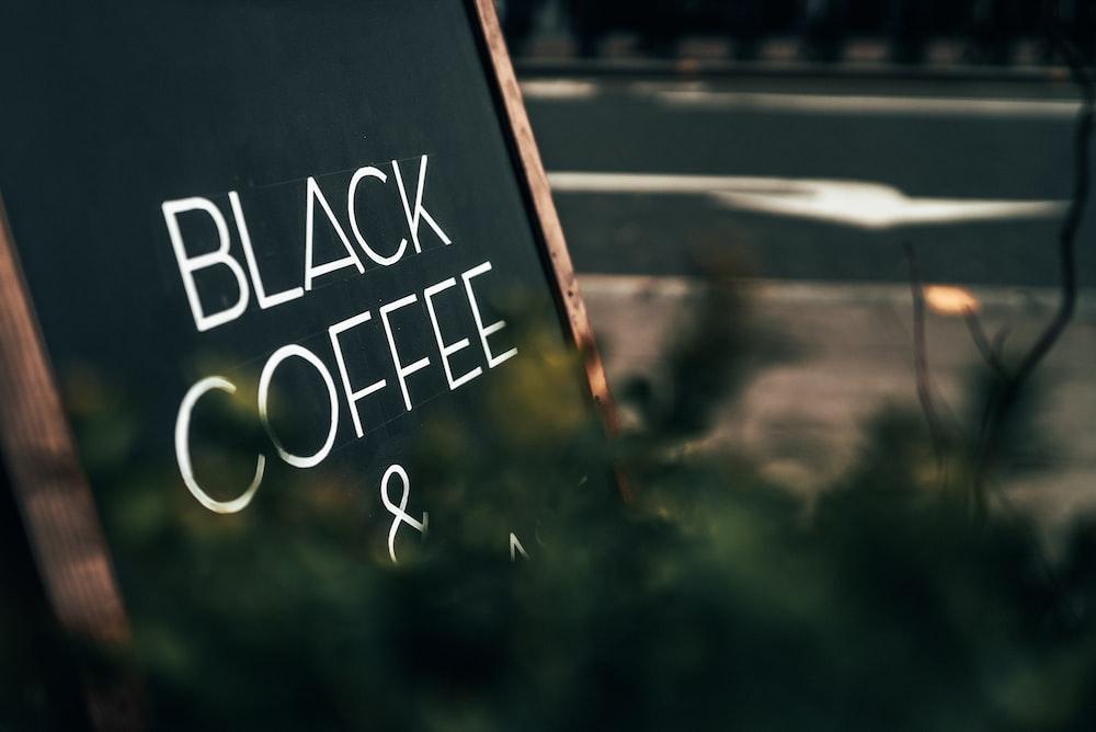 Black Coffee signage near plants
